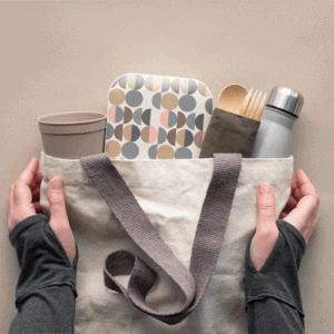sustainable-top-view-zero-waste-packed-lunch-kit-canvas-bag-hands-holding-bag-with-takeaway-lunch-box-bundle-with-bamboo-cutlery-reusable-box-coffee-go-cup-flat-layout-craft-paper